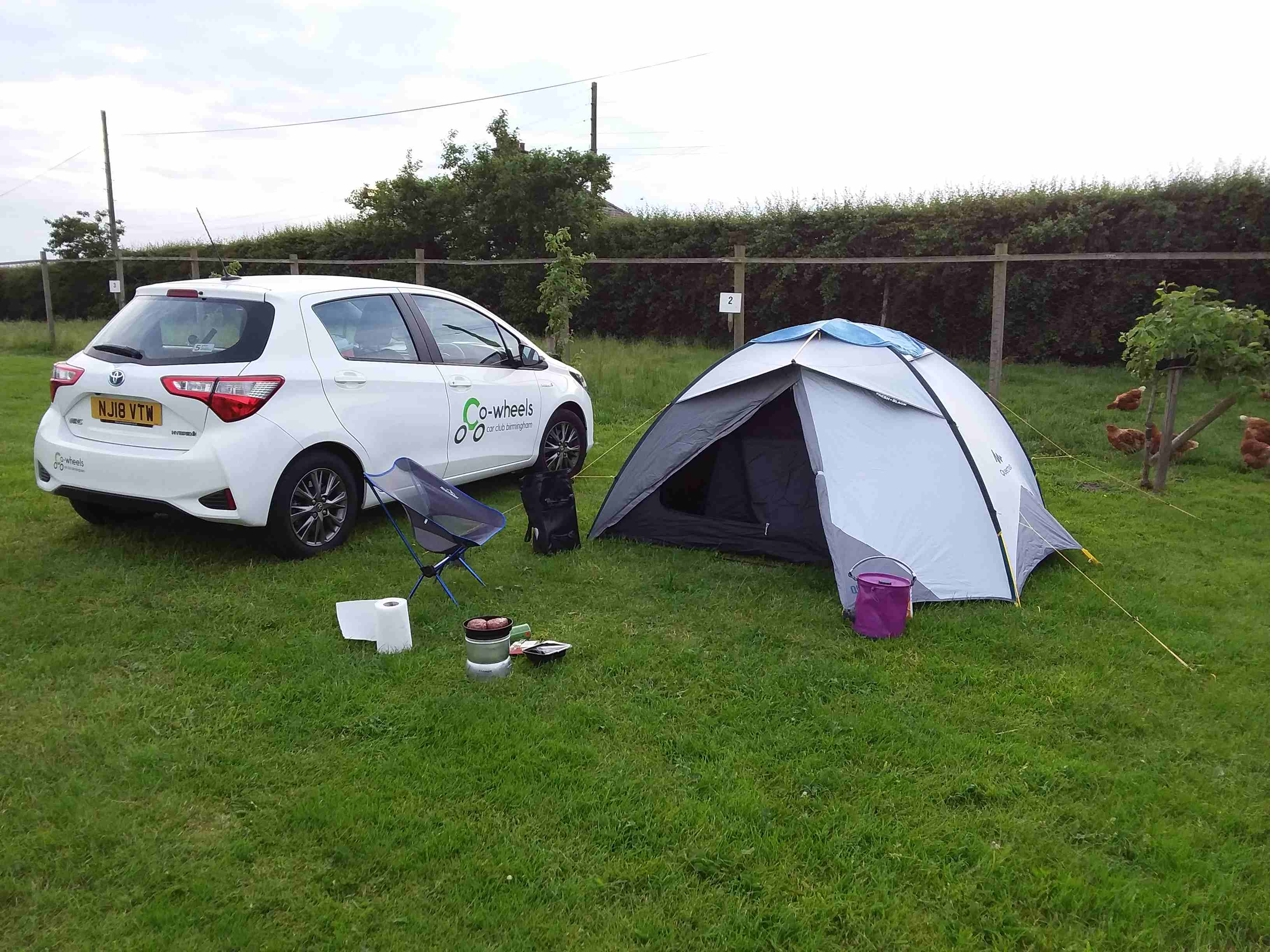 A white Toyota Yaris parked in a camping field next to a white 3-person tent