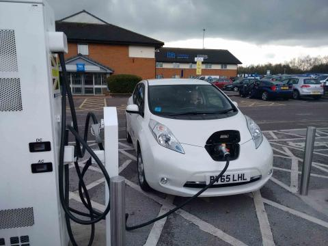 A white Nissan Leaf attached to an Electric Highway CHAdeMo rapid charger at a motorway service station