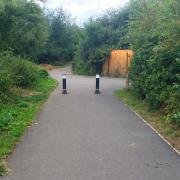 Two bollards preventing motor vehicle access to a shared use lane.
