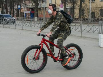 Random guy on a bike wearing a mask